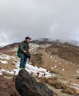 Young man with digital camera on top of the mountain with backpack. concept of traveling and blogging.