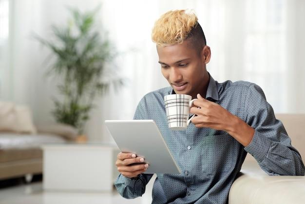 모닝 커피를 마시고 뉴스를 읽는 디지털 태블릿을 가진 청년