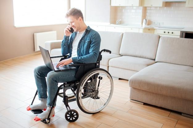 Молодой человек с инвалидностью, сидя на инвалидной коляске. работает на ноутбуке и разговаривает по телефону. один в большой комнате с дневным светом.