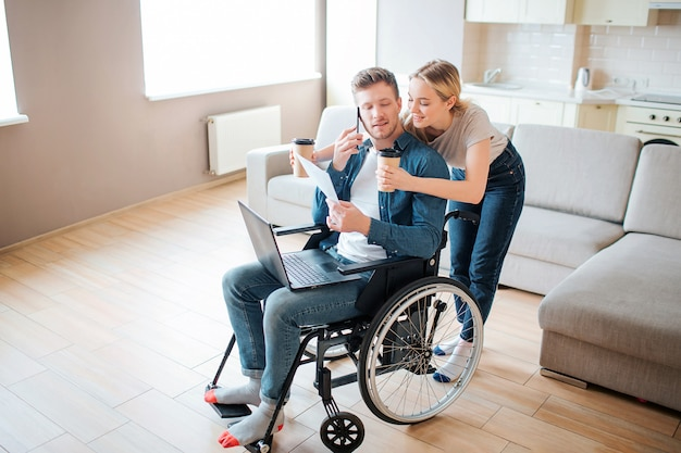 Young man with disability sitting in wheelchair and look back. woman stand behind and hold paper cups of coffee. leaning forward to guy and smile.