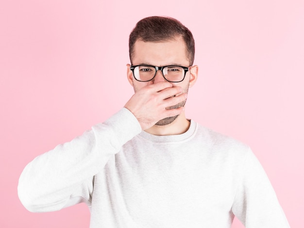 Young man with disgust on his face pinches nose on pink background. negative emotion facial expression.