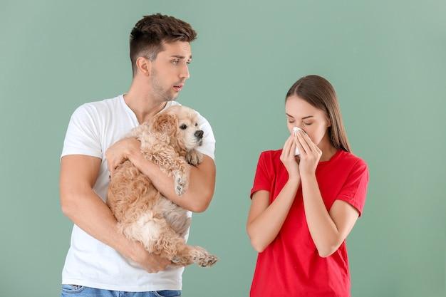 色の背景にペットアレルギーに苦しんでいる犬と彼の妻を持つ若い男