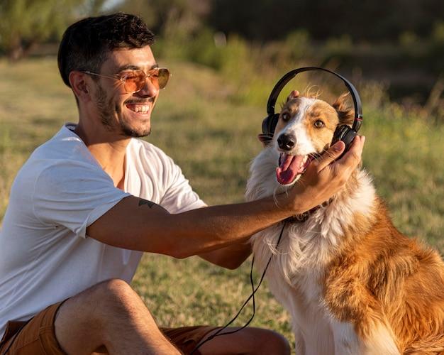 ヘッドフォンで海辺で犬と若い男