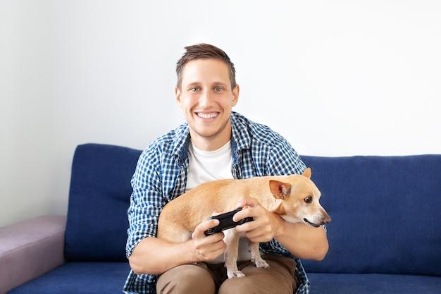 ソファーに座っているとジョイスティックを保持している犬と若い男。テレビでゲームをプレイするジョイスティックを持っている魅力的な剛毛男のクローズアップ。男は家に座って犬とビデオゲームをします。
