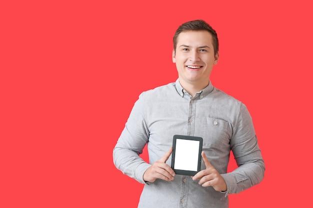 色の背景に電子書籍リーダーを持つ若い男