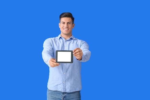 Молодой человек с электронной книгой на цвете