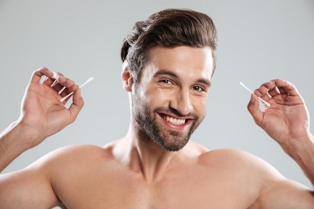 Молодой человек с ушными палочками, улыбаясь в камеру