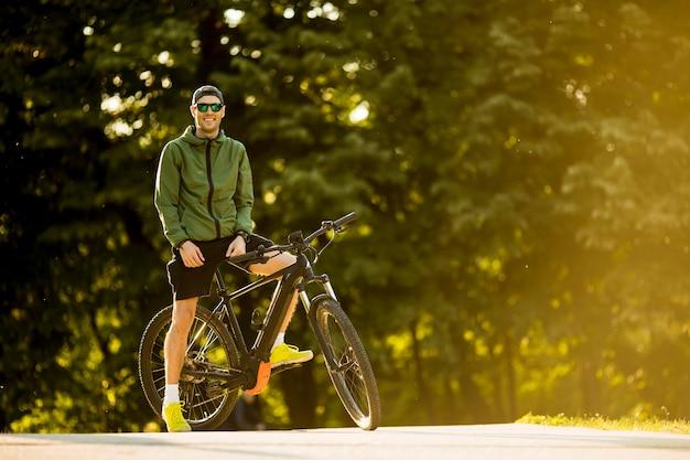 自転車、公園でバッテリー付きマウンテンバイクと若い男