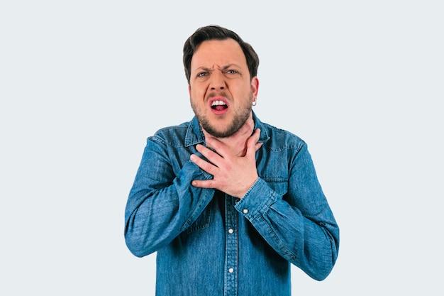목이 아프거나 데님 셔츠로 질식하는 젊은 남자. 격리 된 흰색 배경입니다.
