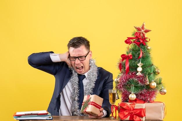 Giovane con gli occhiali che tiene il suo orecchio seduto al tavolo vicino all'albero di natale e regali su giallo