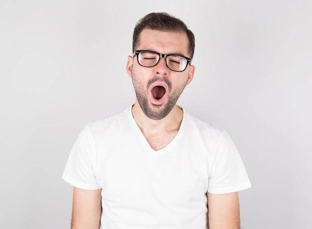 Молодой человек в очках зевает от усталости на белом фоне.