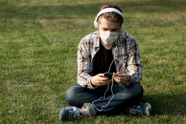 Young man with face mask listening to music