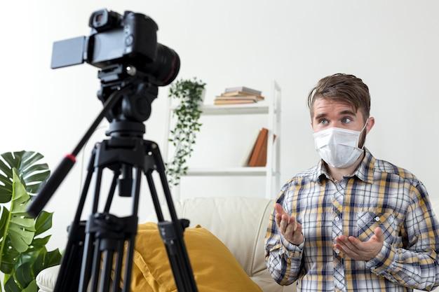 Молодой человек с маской для лица записывает видео дома