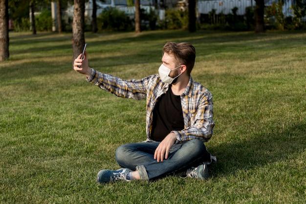 Giovane uomo con la maschera per il viso prendendo un selfie all'aperto