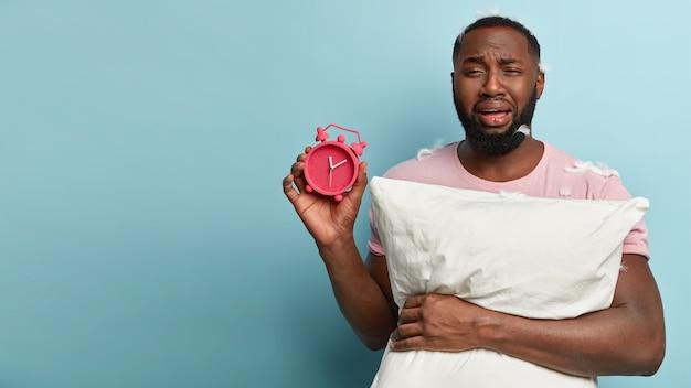 枕と目覚まし時計を保持しているtシャツに羽を持つ若い男