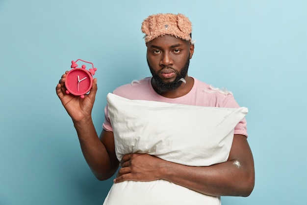 Young man with feathers on t-shirt holding pillow and alarm clock