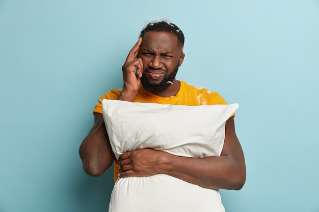 Young man with feathers on t-shirt holding pillow