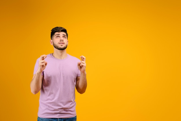 Young man with fingers crossed isolated overyellow background