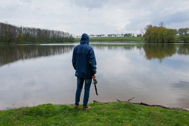 Young man with a fishing rod standing on the lake