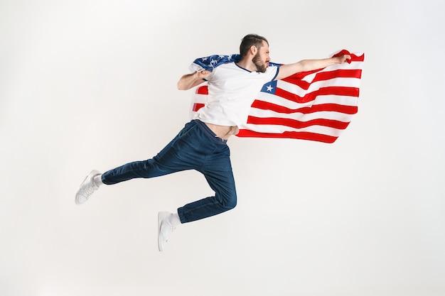白いスタジオで隔離のアメリカ合衆国の旗を持つ青年。