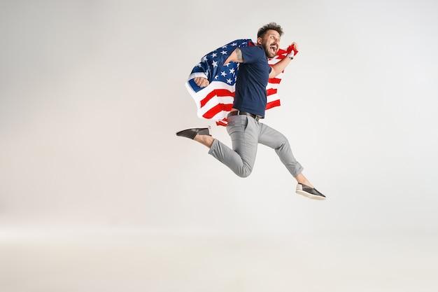 白いスタジオに孤立してジャンプするアメリカ合衆国の旗を持つ若い男。