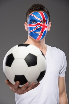 Young man with flag painted on his face to show uk.