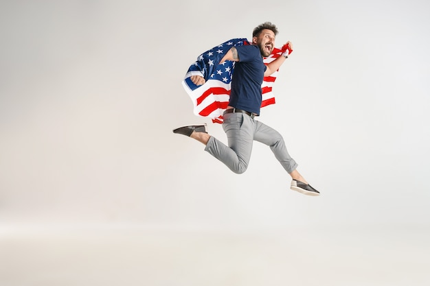 Young man with  flag of the united states of america jumping isolated on white studio.