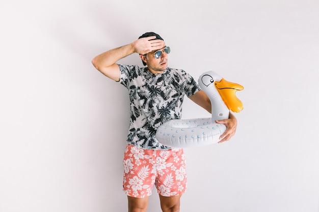 Молодой человек в рубашке с цветочным рисунком, кепке и очках летом с утенком, делая жесты тепла, при дневном свете на белой стене