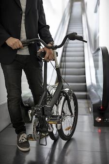 에스컬레이터에 자전거를 접는 젊은 남자