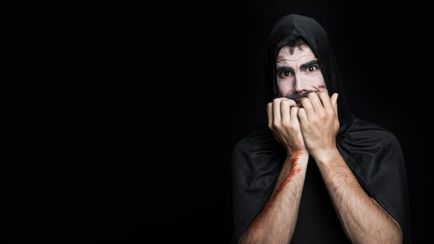 Young man with frightened face in halloween costume posing in studio