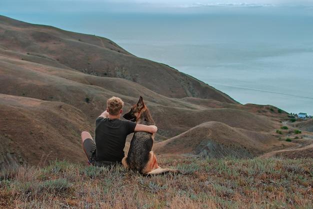 Молодой человек с немецкой овчаркой, глядя на море в горах лучшие друзья путешествуют вместе треккинг, путешествия и концепция деятельности отдых и здоровый активный образ жизни на открытом воздухе социальная дистанция