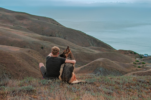Young man with german shepherd dog looking at sea in mountains best friends traveling together trekking travel and activity concept  recreation and healthy active lifestyle outdoors social distance