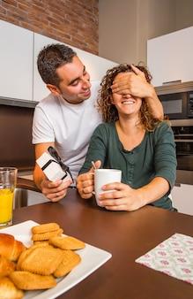 집 부엌에서 아침 식사를 하는 동안 깜짝 선물 상자를 들고 여자 친구의 눈을 감고 있는 젊은 남자