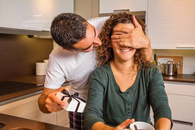 Young man with gift box closing his girlfriend eyes for a surprise while having breakfast on the home kitchen