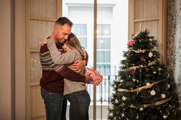 Young man with gift box embracing cheerful woman near christmas tree