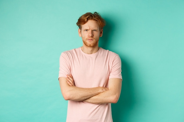 Young man with ginger hair and beard looking offended, feeling insulted and staring at camera, sulking at you, cross arms on chest defensive, standing over turquoise background