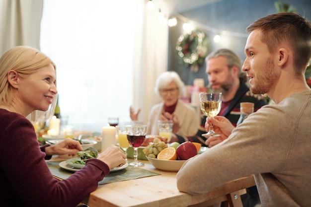 彼の隣に座って新鮮なサラダを食べている彼の幸せな母親にお祝いの乾杯を提供するワインのグラスを持つ若い男