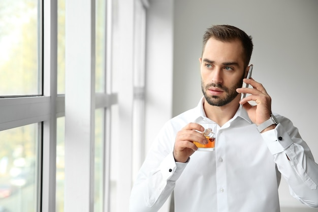 창 근처 전화로 얘기하는 위스키에 유리를 가진 젊은 남자