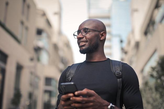 日光の下で携帯電話を保持している眼鏡とバックパックを持つ若い男