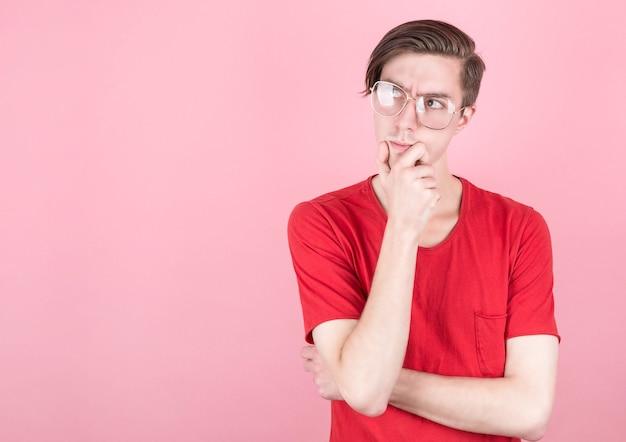 眼鏡と赤いtシャツを持つ若い男は物事を考える