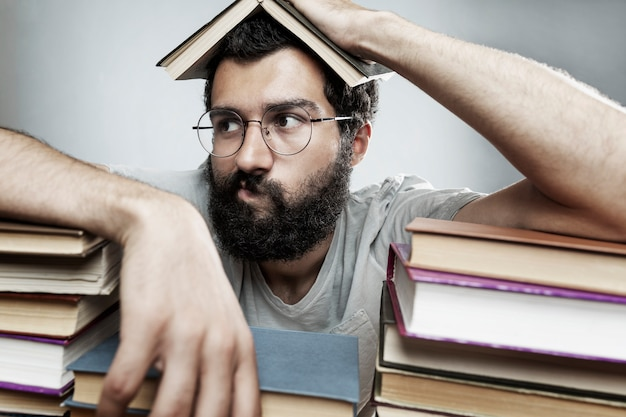 Young man with glasses and a beard sits at a table with stacks of books. training and education.