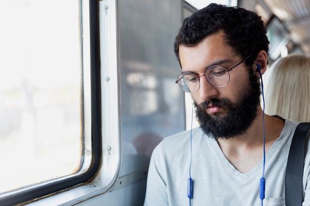 メガネ、ヘッドフォン、ひげを持つ若い男が電車の車に座って音楽を聴きます。観光と旅行。閉じる。