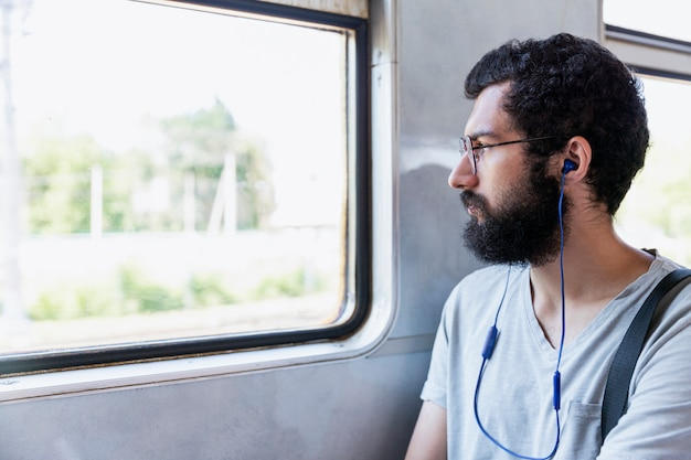 Young man with glasses, headphones and a beard sits in a train car and listens to music. tourism and travel. close-up.