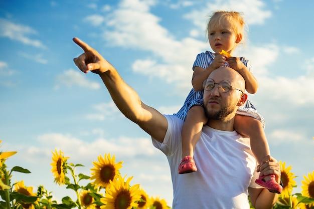 眼鏡をかけた青年が子供を肩に抱き、ひまわり畑の何かを手で指さします。