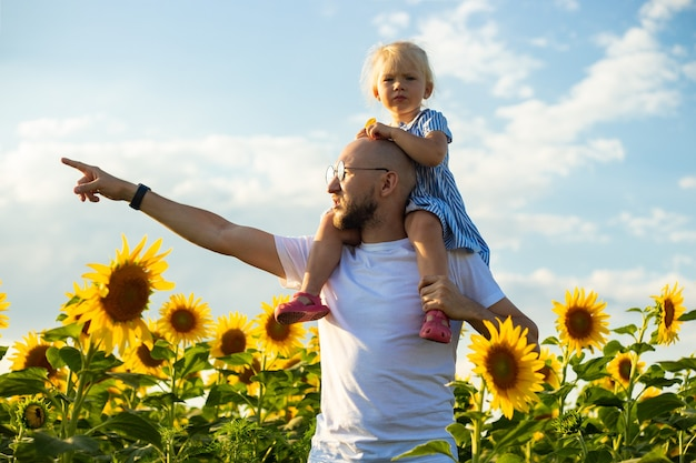 Young man with glasses holds a child on his shoulders and points with his hand to something on a sunflower field.