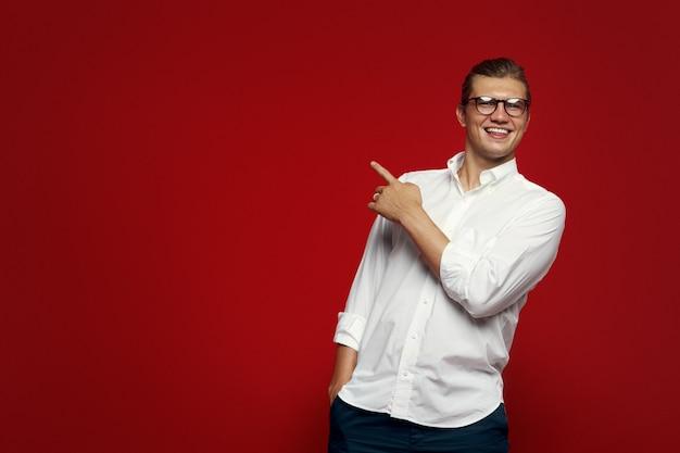 웃 고 왼쪽을 가리키는 흰 셔츠를 입고 안경 젊은 남자