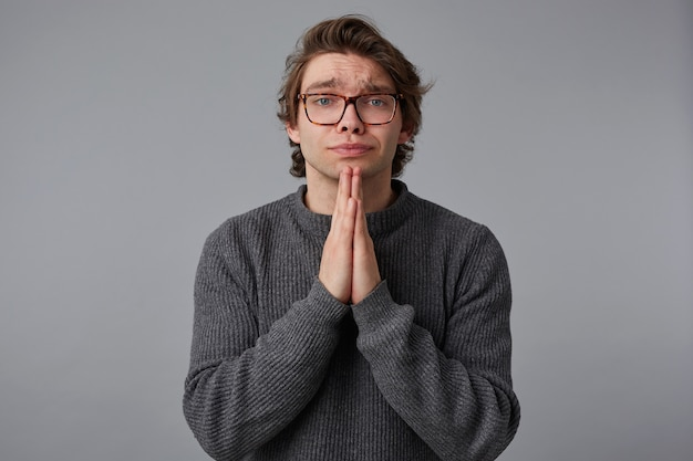 Young man with glasses wears in gray sweater, stands over gray background and looks at the camera, has sorrorful expression, keeps palms in praying gesture.