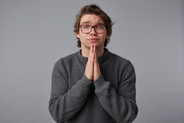 眼鏡をかけた若い男は灰色のセーターを着て、灰色の背景の上に立ってカメラを見て、悲惨な表情をして、手のひらを祈りのジェスチャーに保ちます。