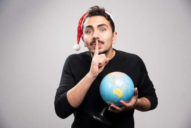 Young man with globe in santa's hat shows a gesture of silence .