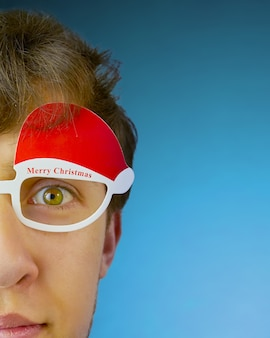Young man with green eyes with glasses with the words merry christmas